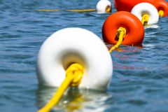 Close-up bright red and white coloers buoys on yellow rope on surface of the water. Depth marks. Safety on the water.  royalty free stock photo