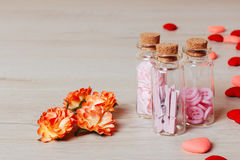 Close up of bright small hearts, spring flowers and glass bottles, contains clothespins and buttons on wooden background. Valentine or holiday composition. Copy Royalty Free Stock Photo