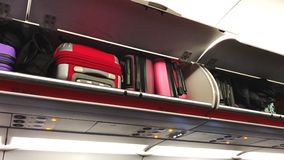 Close-up of bright suitcases lying on the shelves in the plane. Economy class cabin of typical airliner. Slow motion stock video footage