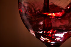 Close-up of brightly red wine poured in the wineglass and abstract splashing against brown background. Macro and horizontal photo. Luxury lifestyle. Still-life Stock Photography