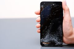 Close-up of broken mobile phone with cracked display. In woman hand royalty free stock photo