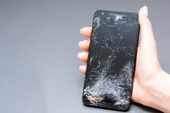 Close-up of broken mobile phone with cracked display. In woman hand stock photo