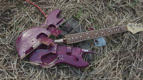 Close up for broken purple guitar lying on withered hay, top view. Stock. Broken electric guitar parts violet deck and