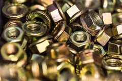 Close-up bronze nuts background. Close-up glossy brass nuts background. Brand new stainless screws or fastener. Industrail abstract concept royalty free stock photos