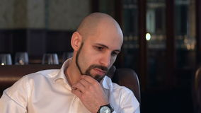 Close-up of a brooding bald man with a beard. Portrait of a bearded businessman stock video footage