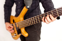 Close up of a brown bass guitar with hands Royalty Free Stock Photography