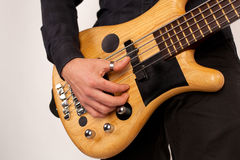 Close up of a brown bass guitar with hands Stock Images