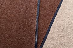 Close-up on brown and beige carpeting stitched with contrasting white thread for the manufacture of carpets for cars in the. Worshop of sewing and detaling of stock image