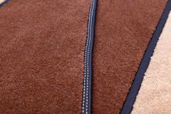 Close-up on brown and beige carpeting stitched with contrasting white thread for the manufacture of carpets for cars in the. Worshop of sewing and detaling of stock photos