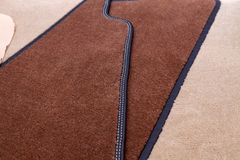 Close-up on brown and beige carpeting stitched with contrasting white thread for the manufacture of carpets for cars in the. Worshop of sewing and detaling of stock photo