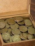 Close up brown box filled with dollar coins Stock Image