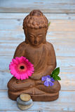 Close up of brown Buddha on used wood With zen stones and flowers Royalty Free Stock Photography
