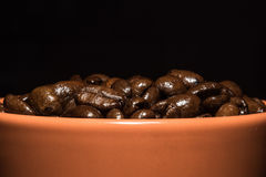 Close-up brown cup with coffee beans. On black background Stock Images