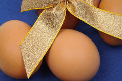 Close-up of brown Easter eggs with gold ribbon. Close-up of brown Easter eggs tied by gold ribbon over blue background Stock Image