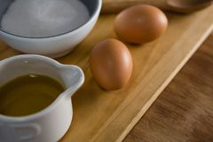 Brown eggs and sugar on chopping board. Close-up of brown eggs and sugar on chopping board Stock Image
