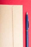 Close-up of brown envelop and pen isolated on red background Stock Photo
