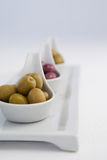 Close up of brown and green olives in white containers. Brown and green olives in containers against white background Stock Photo