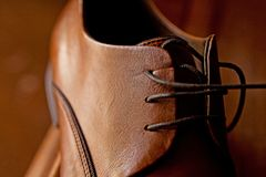 A close up brown leather men`s dress shoes and laces stock images