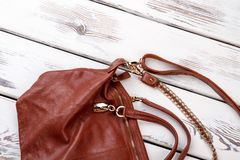 Close up brown leather satchel. Handle on purse. White wooden desks surface background Stock Photos