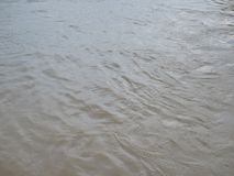Close up of brown muddy murky river surface in a rural area after heavy rain stock photography