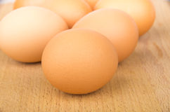 Close up of brown raw chicken eggs on board Royalty Free Stock Photos