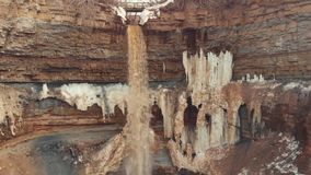 Close-up of brown river water getting into the small waterfall over the brown cliff layers covered with ice and snow. Beginning of the spring stock video footage