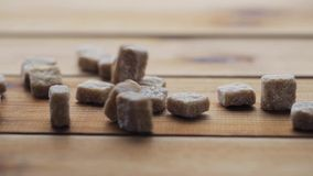 Close up of brown sugar on wooden board or table. Food, junk-food, carbohydrates, cooking and unhealthy eating concept - close up of brown lump sugar on wooden stock footage