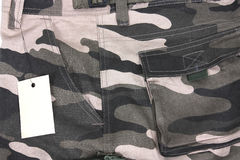 Close-up brown tone camouflage pocket shorts with tag (side) Stock Images