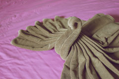 Close up brown towel plait as swan on purple bed Stock Photo