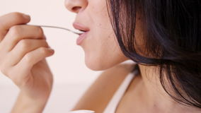 Close up on a brown woman eating a yoghurt stock footage