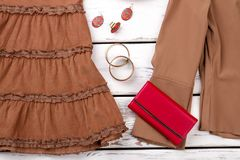 Close up brown women clothes with wallet and accessories. Royalty Free Stock Images