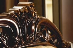 Close-up Brown wooden carved patterns headboard of a double bed. Retro Stylish Bedroom stock photo