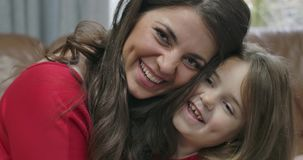 Close-up of brunette Caucasian woman and little girl rubbing noses, looking at camera and smiling. Mother and daughter stock footage