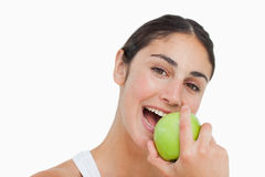 Close-up a brunette eating a green apple Stock Photos