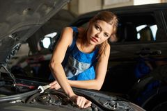 Close-up of brunette female mechanics repairing or inspecting a car. And holds a spanner in her hand. Girl is dressed in working clothes Stock Images