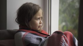 Close-up of a brunette girl covered with a warm blanket sitting on windowsill at home. Caucasian child with fever. Looking at the window sadly. Concept of stock video footage