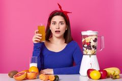 Close up of brunette woman with glass of fresh orange juice in hand. Lady likes healthy eating, making smoothie at home. Surprised royalty free stock photo