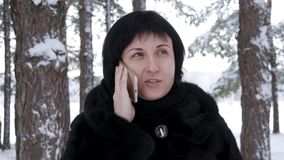 Close-up of a brunette woman standing against a forest or park on a winter day. The girl is holding her smartphone and stock video footage