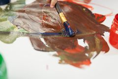 Multicolored gouache on white sheet and brush for drawing in action. royalty free stock image