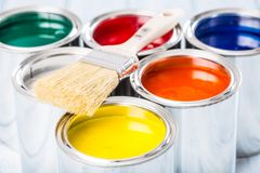 Close-up brush lying on multicolored paint cans royalty free stock photos