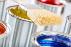 Close-up brush lying on multicolored paint cans.  stock photos