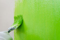 Close up brush painting green color on wall Royalty Free Stock Images