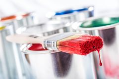 Close-up brush with red color lying on paint can royalty free stock photo