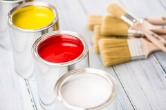 Close-up brushes lying on multicolored paint cans.  royalty free stock photos