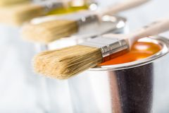 Close-up brushes lying on multicolored paint cans stock images