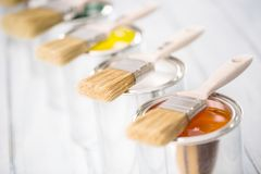 Close-up brushes lying on multicolored paint cans.  royalty free stock images