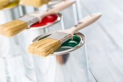 Close-up brushes lying on multicolored paint cans.  stock images