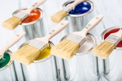 Close-up brushes lying on multicolored paint cans.  royalty free stock photography