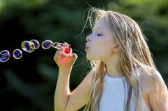 Close-up of bubble-blowing young girl 11, with long blond hair, blowing brightly colored bubbles in the garden. stock image