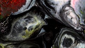 Close-up of bubbling black ink. On colorful surface of milk with paint stains appears bubbly black ink. Bubbling black. Oil stains contaminate colorful liquid royalty free stock photography